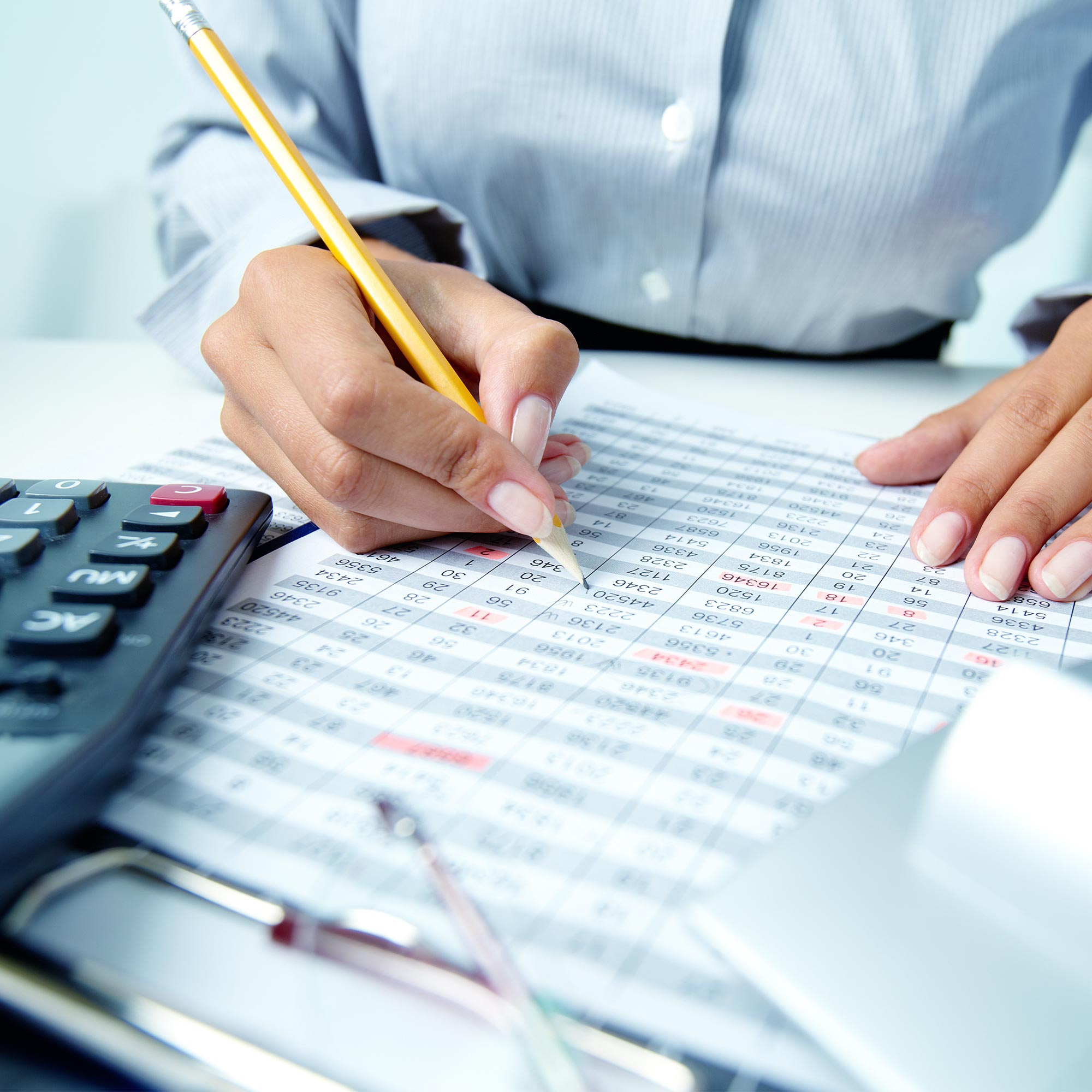 Accountant business woman's hands. Counting numbers with calculator and a pencil in hands. Accounting, tayes and payroll services.